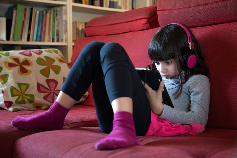 girl listens through headphones