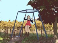 A girl happily sitting on a swing.